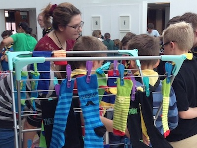 Photograph of student demonstrator playing sock chromosome game with a scout troop