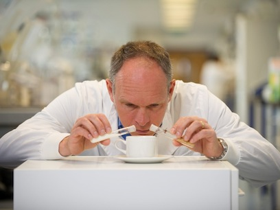 Photograph of Richard in a lab coat preparing a cup of coffee in the manner of a mad scientist